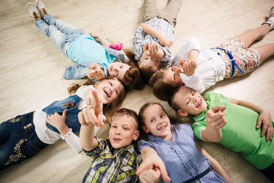 Group of happy kids laying in star shape on the floor with lifted hands