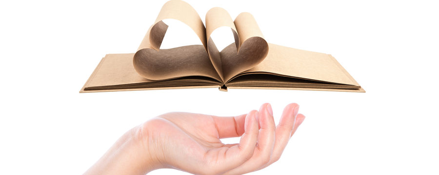 Beautiful woman  hand holding Book with opened pages of shape of heart