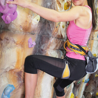 Girl exercises on indoor rock climber